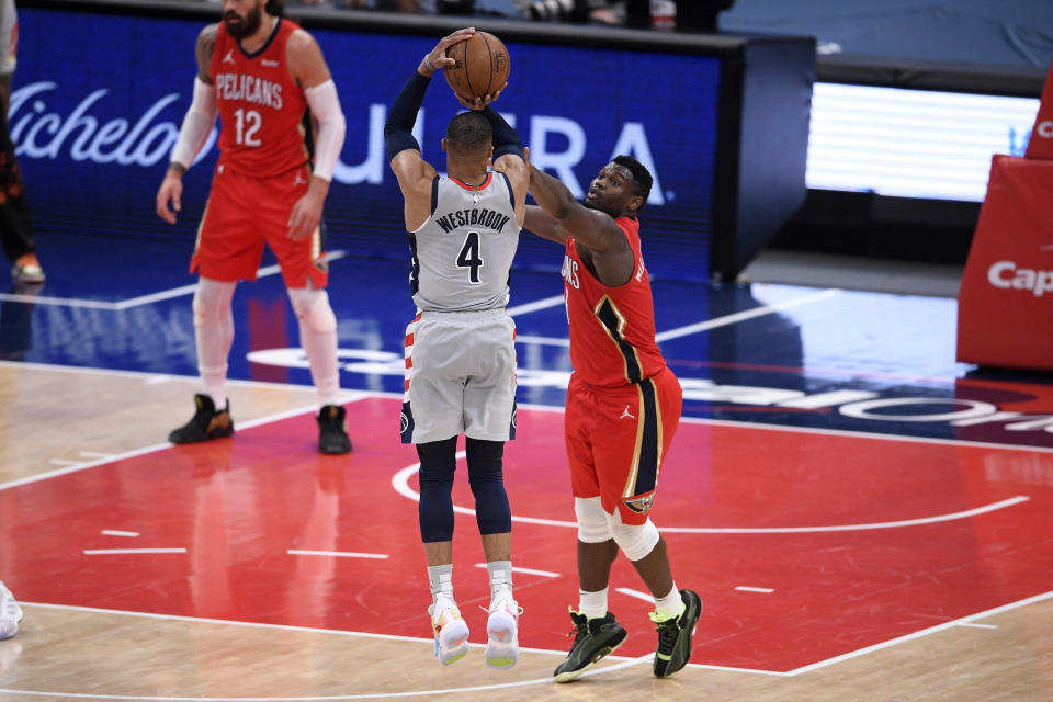 Washington Wizards guard Russell Westbrook (4) shoots against New Orleans Pelicans forward Zion Williamson, right, late in the overtime of an NBA basketball game Friday, April 16, 2021, in Washington. Williamson was called for a foul on the play. (AP Photo/Nick Wass)
