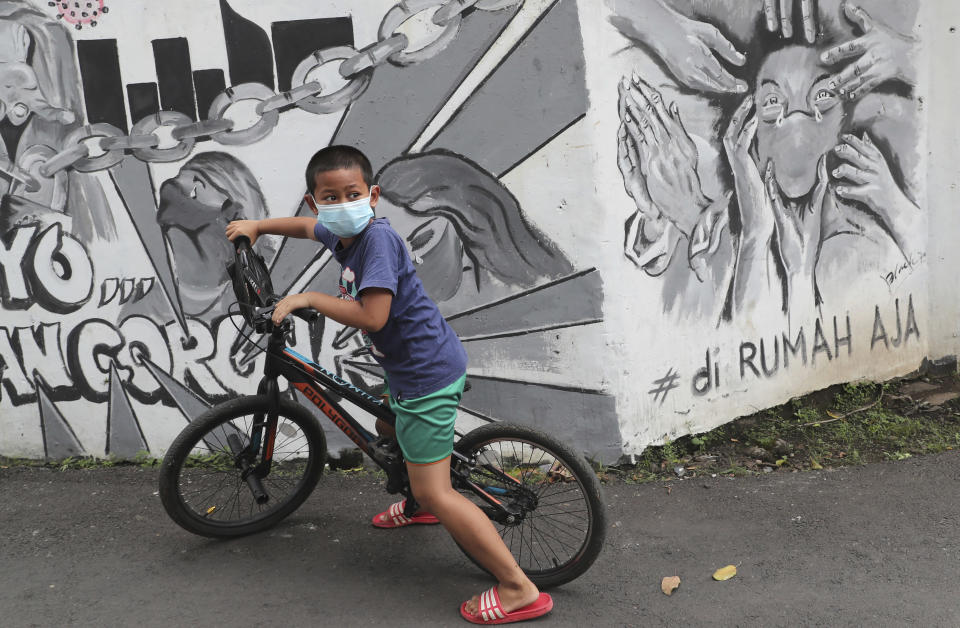 "A cyclist wearing a face mask rides past a coronavirus-themed mural in Jakarta, Indonesia, Wednesday, Nov. 25, 2020. Writings on the mural read ""Stay at Home."" (AP Photo/Tatan Syuflana)"