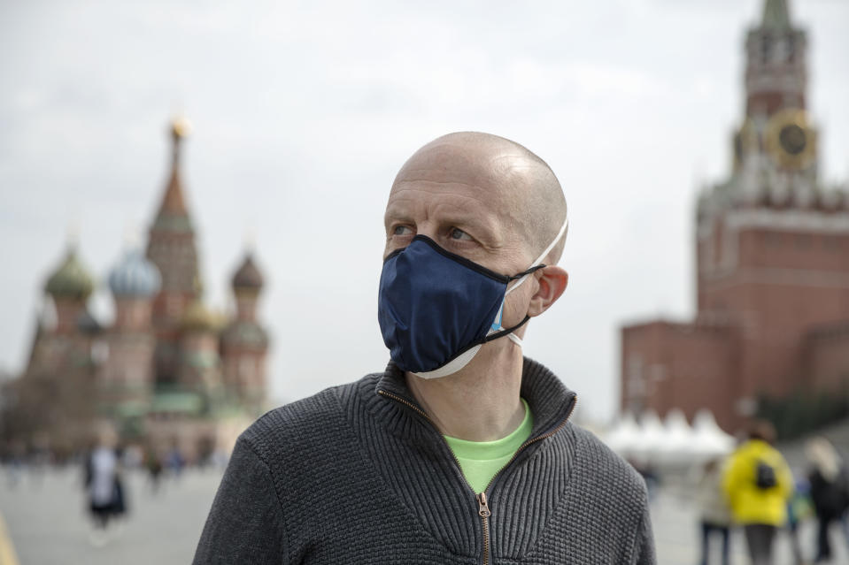 """Uwe Keim wearing a face mask to protect against coronavirus walks in Red square after getting the first shot of Russia's Sputnik V coronavirus vaccine in Moscow, Russia, Friday, April 16, 2021. Keim, 46-year-old software developer from Stuttgart, told The Associated Press after getting his jab that he isn't worried about depriving some Russian of their shot, as he believes """"there are more vaccines available here in Russia than is demanded by the people here."""" (AP Photo/Pavel Golovkin)"""