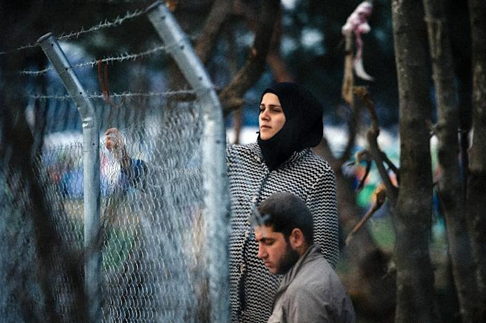 A couple stands behind a fence as refugees and migrants wait to cross the Greek-Macedonian border near the town of Gevgelija on March 3, 2016 (AFP Photo/Dimitar Dilkoff)