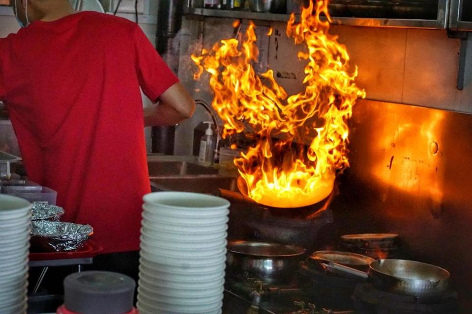 man wok-frying with flames in wok