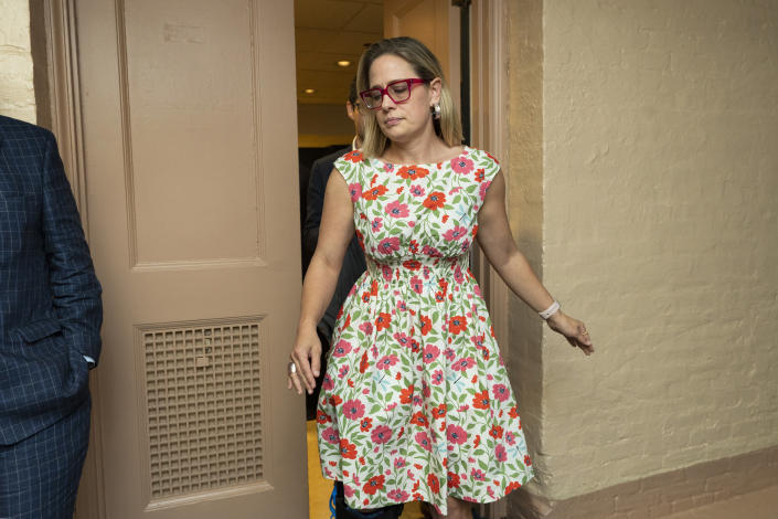 FILE - In this June 22, 2021, file photo, Sen. Kyrsten Sinema, D-Ariz., leaves a closed-door bipartisan infrastructure meeting with a group of senators and White House aides on Capitol Hill in Washington. More than her shock of purple hair or unpredictable votes Sinema is perhaps best known for doing the unthinkable in Washington: spending time on the Republican side of the aisle. Her years in Congress have been a whirlwind of political style and perplexing substance, an anti-war liberal-turned-deal-making centrist who now finds herself at the highest levels of power.(AP Photo/Manuel Balce Ceneta)
