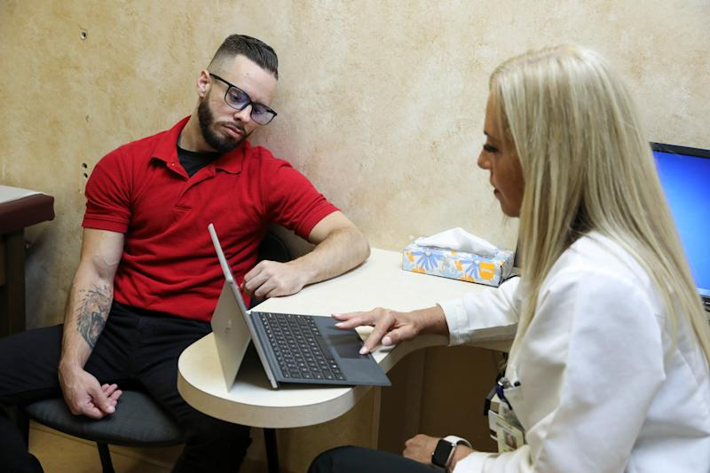 Cystic fibrosis patient Garrett Greene, of Coconut Creek. Fla., speaks with his new pain management doctor, Melanie Rosenblatt, during his appointment on Monday, June 17, 2019, in Boca Raton, Fla.