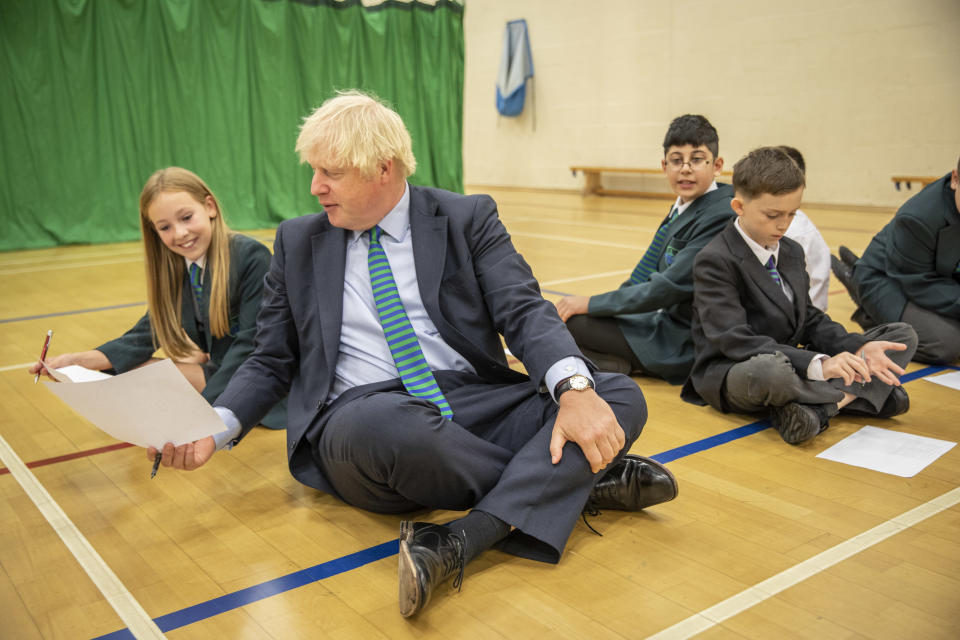 COALVILLE, ENGLAND  - AUGUST 26: British Prime Minister Boris Johnson, wearing the school tie he was presented with on arrival, takes part in a getting to know you induction session in the gym with year 7 pupils on their first day back at school during a visit to Castle Rock school on August 26, 2020 in Coalville, United Kingdom. (Photo by Jack Hill - WPA Pool/ Getty Images)
