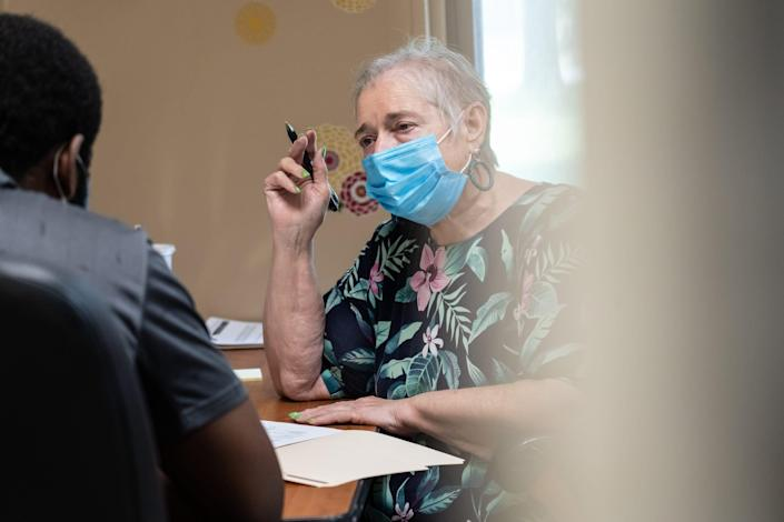 Macomb County Rotating Emergency Shelter Team (MCREST) case manager Jane Mahoney asks questions to Taijh Robinson of Warren while seeing how their program can help him out after becoming homeless following a fire to his mother's home on July 26, 2021 at the MCREST building in Roseville.