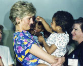 """FILE - In this April 24, 1991 file photo, Britain's Princess Diana, the Princess of Wales, hugs and plays with an HIV positive baby in Faban Hostel, San Paulo, on the second day of her visit to Brazil.For someone who began her life in the spotlight as """"Shy Di,"""" Princess Diana became an unlikely, revolutionary during her years in the House of Windsor. She helped modernize the monarchy by making it more personal, changing the way the royal family related to people. By interacting more intimately with the public -- kneeling to the level of children, sitting on edge of a patient's hospital bed, writing personal notes to her fans -- she set an example that has been followed by other royals as the monarchy worked to become more human and remain relevant in the 21st century. (AP Photo/Dave Caulkin, File)"""
