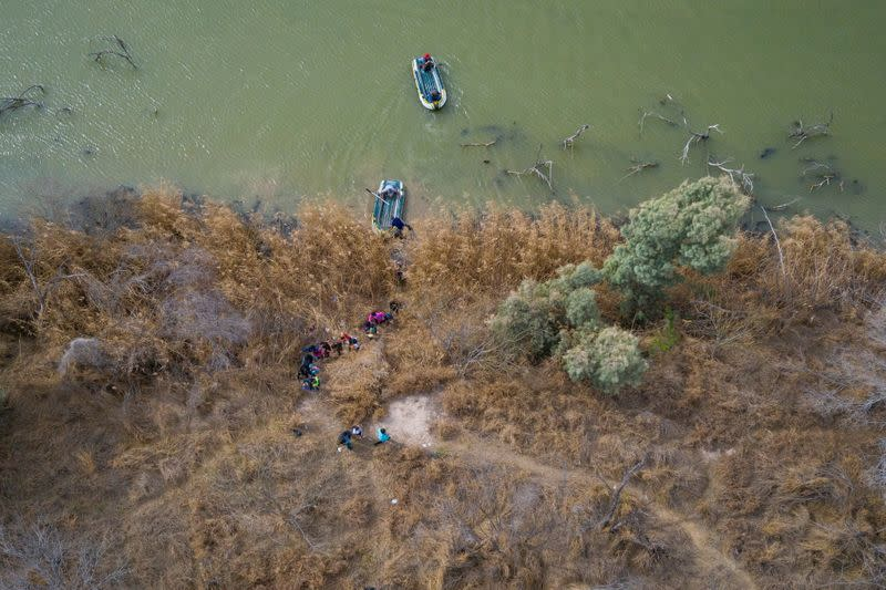 Migrants climb the banks of the Rio Grande River into the United States as smugglers on rafts prepare to return to Mexico in Penitas, Texas