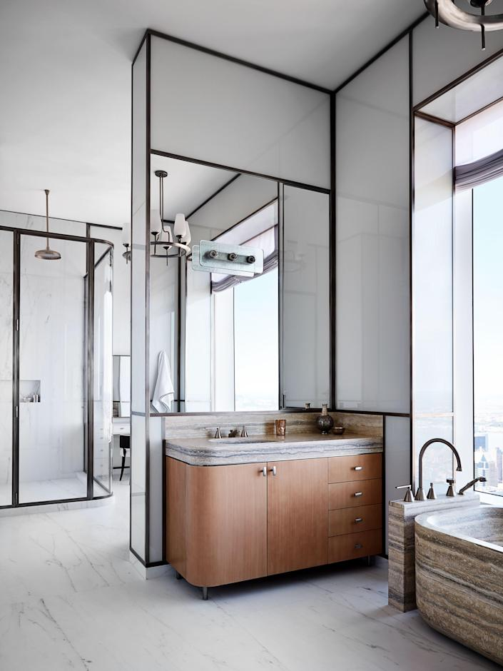 The primary bath has a Franco Albini sconce, a Paavo Tynell chandelier, P.E. Guerin fittings, and walls of back-painted glass.