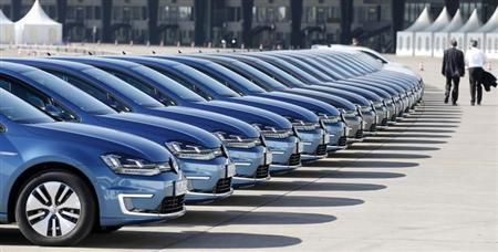 People pass row of Volkswagen e-Golf cars during company's annual news conference in Berlin