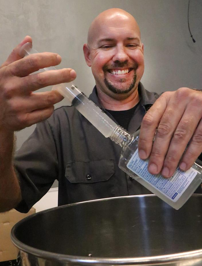 Copper Bottom Craft Distillery owner Jeremy Craig, laughs while he fills small bottles with hand sanitizer, Wednesday March 18, 2020 as the Holly Hill, Florida, distillers use some of their product to make hand sanitizer and give it away to those in the community during the Coronavirus outbreak.