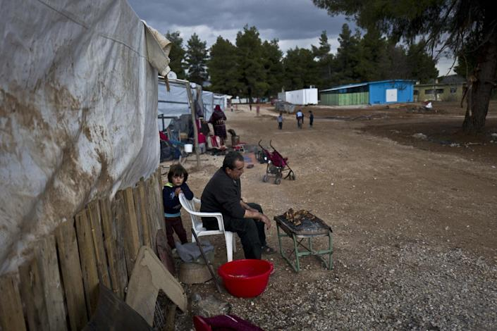 A Syrian refugee man prepares chicken on a grill outside his shelter at the refugee camp of Ritsona about 86 kilometers (53 miles) north of Athens, Thursday, Jan. 5, 2017. Over 62,000 refugees and migrants are stranded in Greece after a series of Balkan border closures and an European Union deal with Turkey to stop migrant flows. (AP Photo/Muhammed Muheisen)