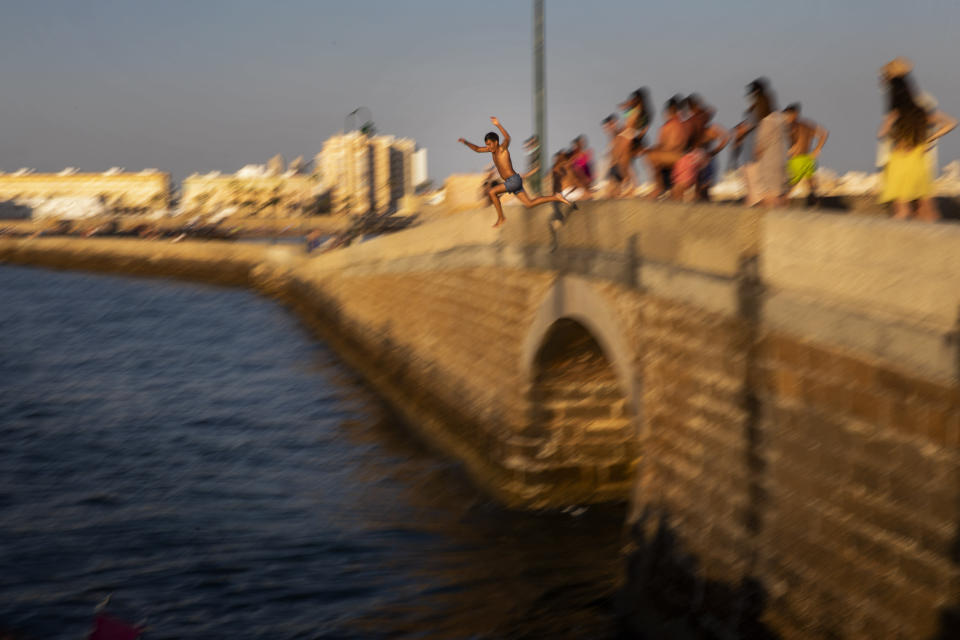 A boy jumps into the water from an ancient bridge leading to the San Sebastian castle in Cadiz, south of Spain, on Friday, July 23, 2020. With the coronavirus rebounding in parts of Spain, it appears that several regions have not adequately prepared to trace new infections in what was supposed to be an early detection system to prevent a new cascade of cases. (AP Photo/Emilio Morenatti)
