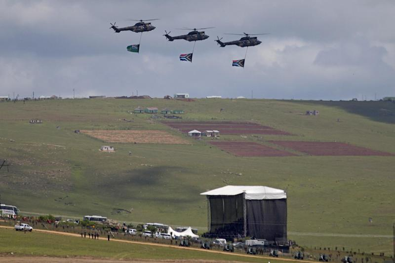 Three helicopters fly over the grave site during the burial of former South African President Nelson Mandela in his hometown Qunu, South Africa, Sunday Dec. 15, 2013. (AP Photo/Peter Dejong)