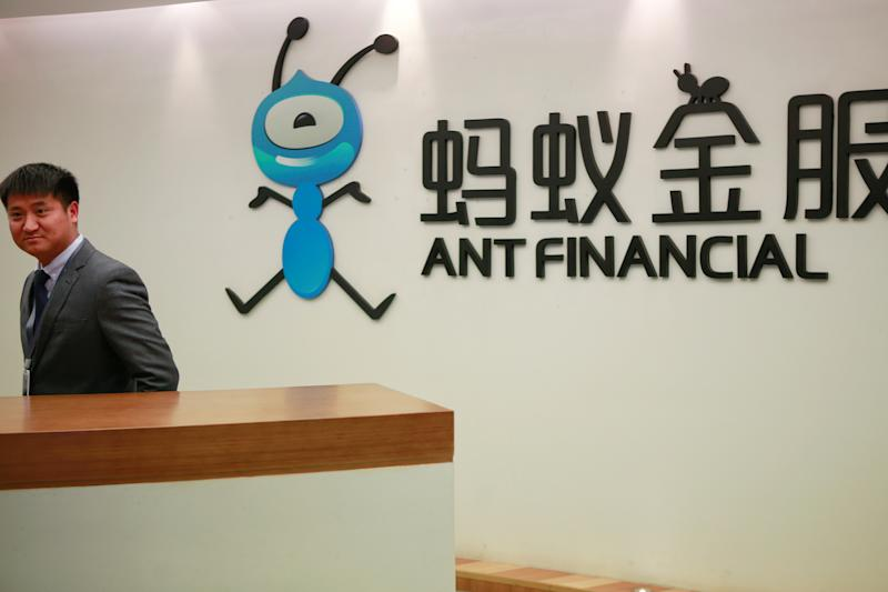FILE PHOTO: Employee stands next to the logo of Ant Financial Services Group at its headquarters in Hangzhou