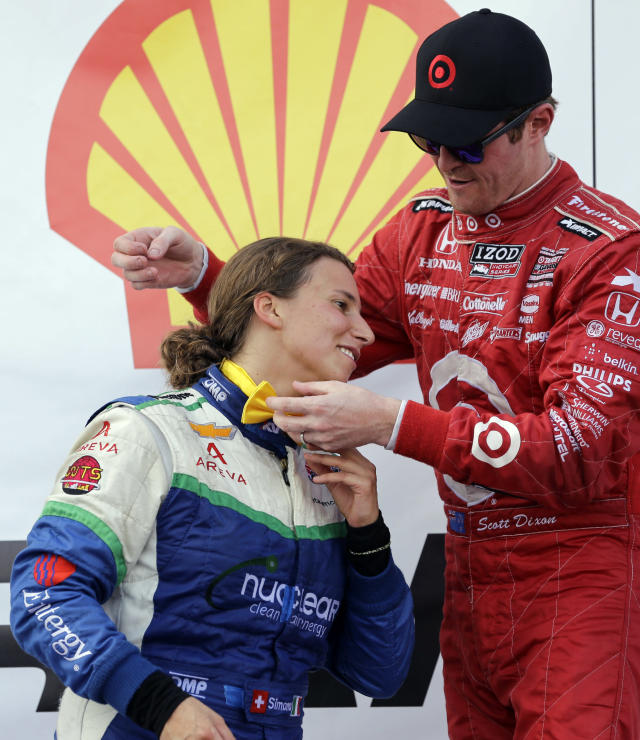Scott Dixon, right, of New Zealand, helps put a bow tie on Simona De Silvestro, of Switzerland, while standing on the victory platform after the first IndyCar Grand Prix of Houston auto race, Saturday, Oct. 5, 2013, in Houston. Dixon finished first, and De Silvestro finished second. (AP Photo/David J. Phillip)