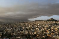 Smoke from a wildfire north of the Greek capital, spreads over Athens, Greece, Tuesday, Aug. 3, 2021. Hundreds of residents living near a forest area north of Athens fled their homes Tuesday as a wildfire reached residential areas as Greece grappled with its worst heatwave in decades. (AP Photo/Aggelos Barai)