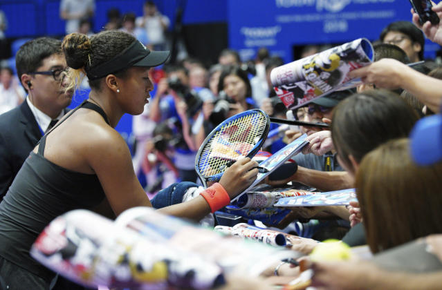 Naomi Osaka of Japan signs her autograph to fans after defeating Dominika Cibulkova of Slovakia during the second round match of Pan Pacific Open women's tennis tournament in Tokyo Wednesday, Sept. 19, 2018. (AP Photo/Eugene Hoshiko)
