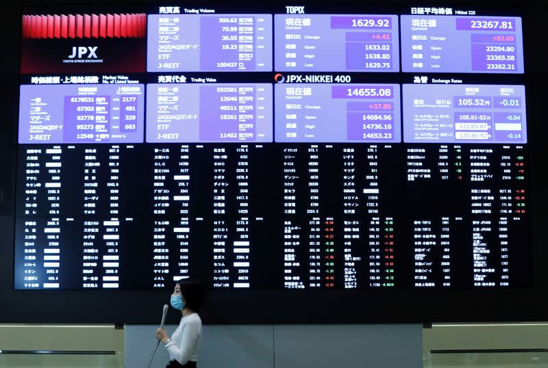 A TV reporter stands in front of a large screen showing stock prices at the Tokyo Stock Exchange after market opens in Toky