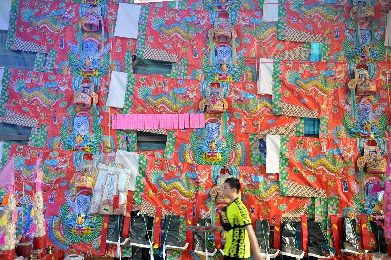 A man walks pass paper clothing put up as offerings during the Hungry Ghost Festival in George Town September 8, 2017. — Picture by KE Ooi
