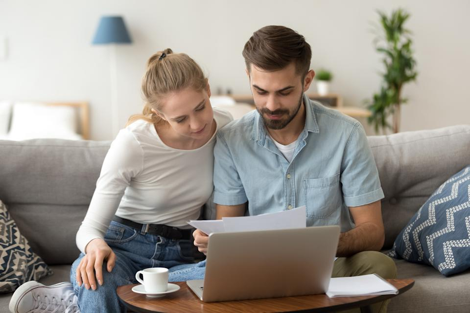 Young serious couple holding reading financial documents checking paying household bills online on laptop, managing finances taxes, reviewing bank accounts, planning budget expenses at home together
