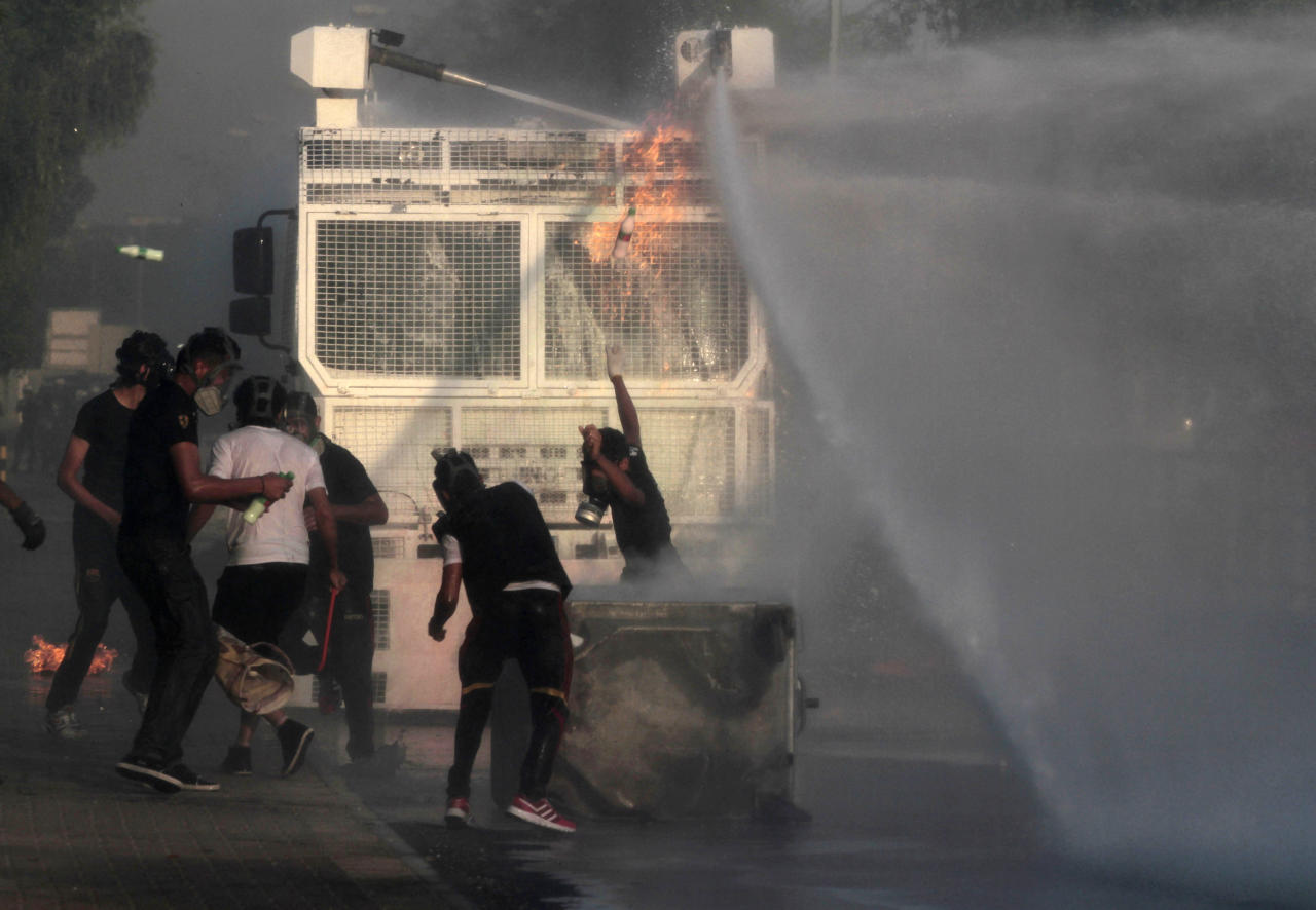 Bahraini anti-government protesters, masked against tear gas, throw bottles of paint and petrol bombs at a police water cannon truck during clashes with riot police in Sanabis, Bahrain, on Friday, Oct. 5, 2012. Riot police used water cannons and tear gas on Friday to disperse hundreds of anti-government protesters trying to reach a heavily guarded site that was once the hub of their uprising. (AP Photo/Hasan Jamali)