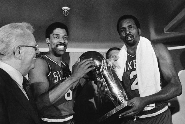 Julius Erving, left, and Moses Malone, right, hold the 1983 NBA Finals after their Philadelphia 76ers defeated the Los Angeles Lakers in four straight games. (AP)