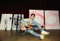 Henry Lau poses with his artworks in his studio
