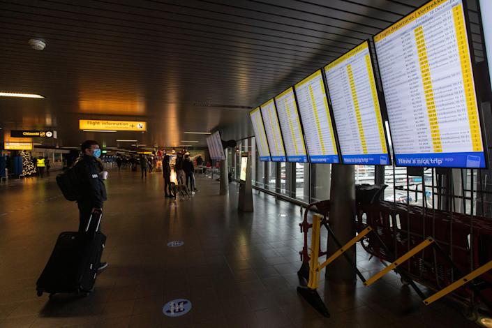 A traveler wearing a face mask checks the flight departures at Schiphol Airport, near Amsterdam, Netherlands, Friday, Dec. 18, 2020. Starting Saturday, the European Union member state will prohibit entry among the unvaccinated and require testing and quarantine period for vaccinated travelers.