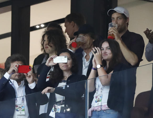 Singer Mick Jagger of the Rolling Stones, in black baseball hat, drinks a pint during the semifinal match between Croatia and England at the 2018 soccer World Cup in the Luzhniki Stadium in, Moscow, Russia, Wednesday, July 11, 2018. (AP Photo/Alastair Grant)