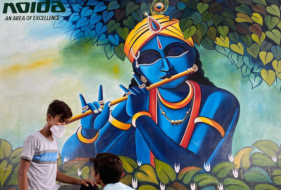 Youths talk as they sit beside a graffiti of Hindu God Krishna in Noida on August 11, 2020 on the eve of the 'Janmashtami' festival which marks the birth of the Hindu God Lord Krishna. (Photo by Money SHARMA / AFP) (Photo by MONEY SHARMA/AFP via Getty Images)