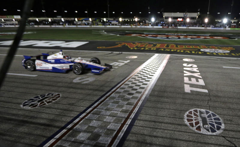 Helio Castroneves approaches the finish line as he wins the IndyCar auto race Saturday, June 8, 2013, at Texas Motor Speedway in Fort Worth, Texas. (AP Photo/Tim Sharp)