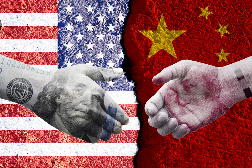 US dollar and China Yuan banknote print screen on handshake with both flags countries.It is symbol of economic tariffs trade war and tax barrier between United States of America and China.