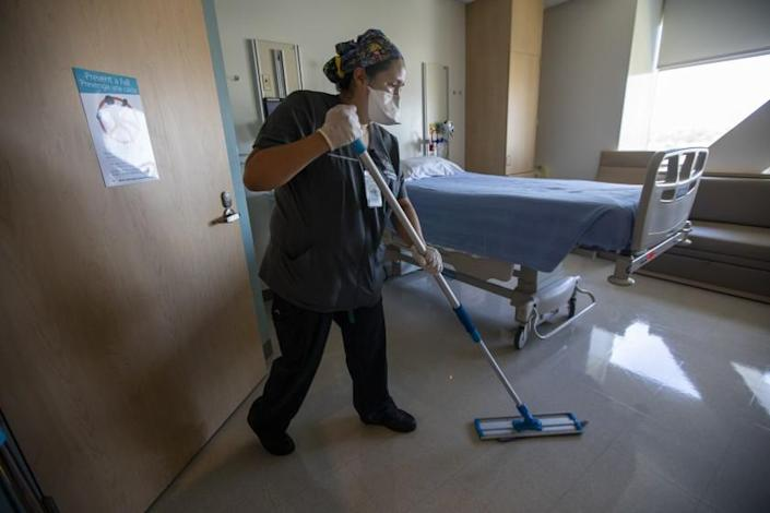 LOS ANGELES, CA - MAY 05: Guadalupe Padilla with the envinmental services depatment cleans an empty room on the fifth floor at Martin Luther King Jr. Community Hospital on Wednesday, May 5, 2021 in Los Angeles, CA. In dramatic shift, California COVID-19 hospitalizations are lowest since pandemic's start. She says she has worked here nearly five years. She worked at the hospital cleaning throughout the pandemic. (Francine Orr / Los Angeles Times)