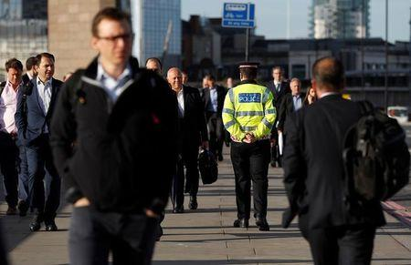 FILE PHOTO: Commuters walk past a City of London police officer standing on London Bridge after is was reopened following an attack which left 7 people dead and dozens of injured in central London