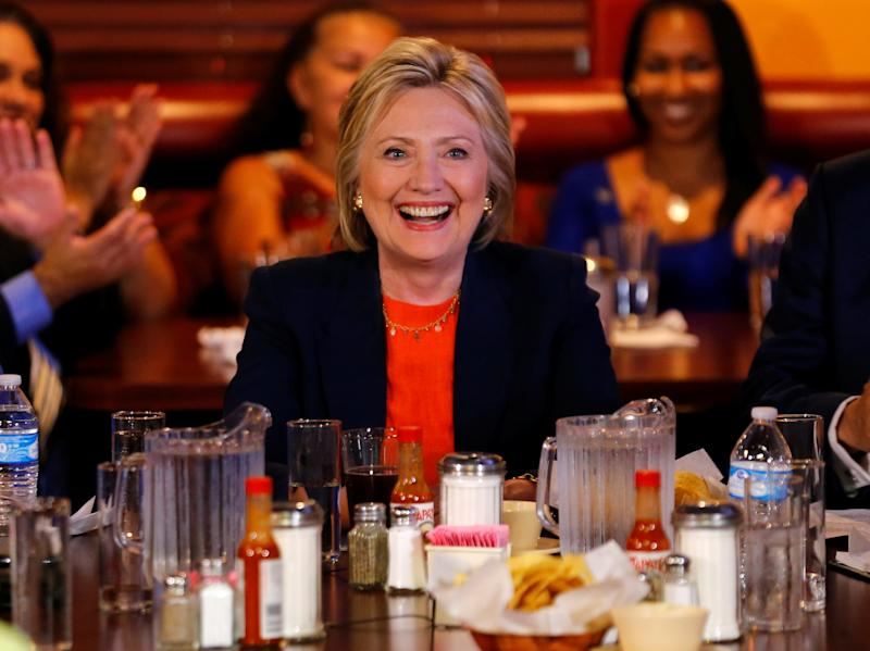 Clinton smilesamid hot sauce bottles while making a campaign stop at a restaurant in Perris, California on June 2, 2016. (Mike Blake / Reuters)