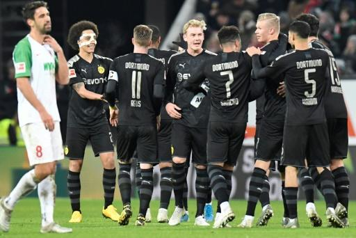 Dortmund's Norwegian forward Erling Braut Haaland (3rdR) is congratulated by teammates after scoring a hat-trick on his debut in the 5-3 win at Augsburg on Saturday