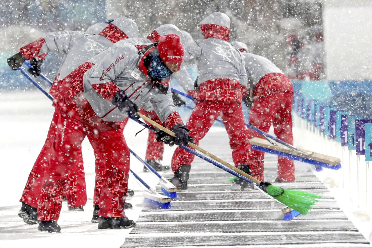 <p>Course workers clear the snow off of the shooting range during the Women's 4x6km Biathlon Relay at the 2018 Winter Olympics in PyeongChang, South Korea, Feb. 22, 2018.<br /> (AP Photo/Andrew Medichini) </p>