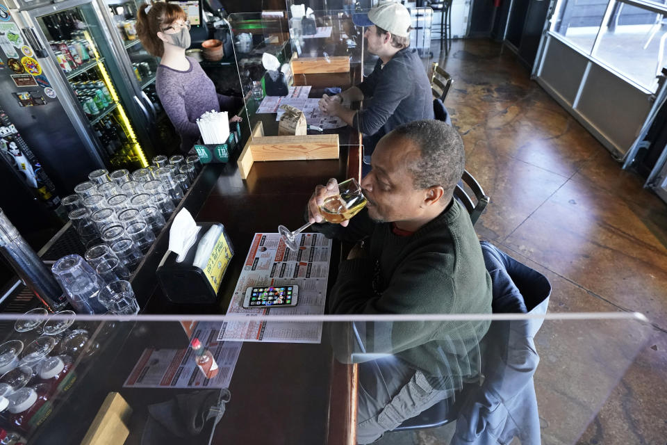 Darrell Boyd sips a glass of wine at the Winking Lizard Tavern, Monday, Nov. 16, 2020, in Beachwood, Ohio. Ohio Governor Mike DeWine issued a new health warning Sunday to limit mass gatherings. (AP Photo/Tony Dejak)