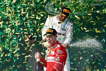 Formula One - F1 - Australian Grand Prix - Melbourne, Australia - 26/03/2017 - Ferrari driver Sebastian Vettel of Germany (front) sprays champagne alongside second-placed Mercedes driver Lewis Hamilton of Britain on the podium. REUTERS/Brandon Malone