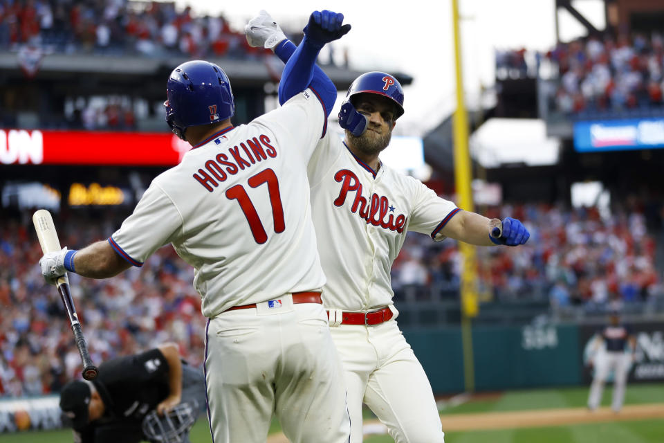 Philadelphia Phillies' Bryce Harper, right, and Rhys Hoskins celebrate after Harper's home run during the seventh inning of a baseball game against the Atlanta Braves, Saturday, March 30, 2019, in Philadelphia. (AP Photo/Matt Slocum)