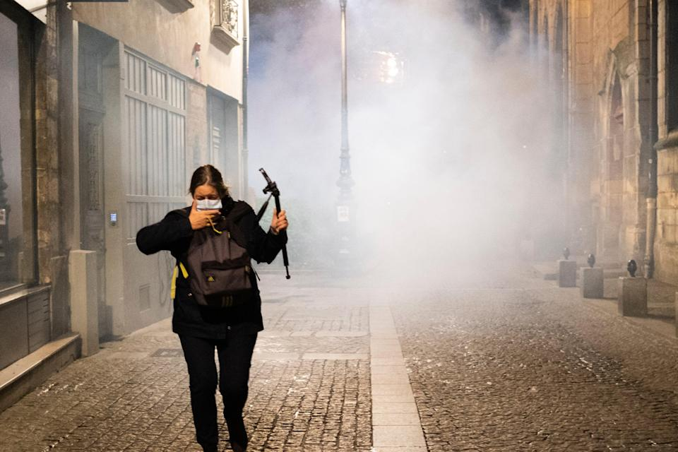 A woman flees tear gas after police removed tents set up by migrants in Paris. Police are under government orders to explain themselves after officers were filmed tossing migrants out of tents while evacuating a makeshift camp in the French capital. (Alexandra Henry/Utopia56 via AP) (AP)