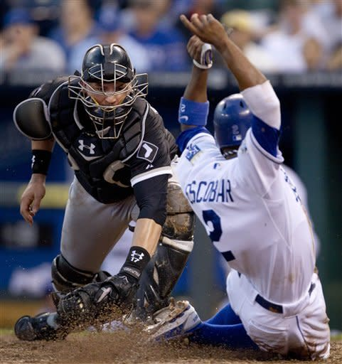 Kansas City Royals' Alcides Escobar (2) beats the tag by Chicago White Sox catcher Tyler Flowers, left, during the fifth inning of a baseball game at Kauffman Stadium in Kansas City, Mo., Saturday, Aug. 18, 2012. Escobar scored on a single by teammate Billy Butler. (AP Photo/Orlin Wagner)