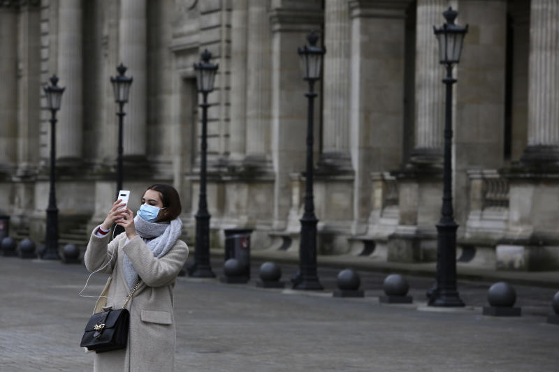 A tourist wearing a mask makes a selfie outside the Louvre museum Friday, Feb. 28, 2020 in Paris. . The world is scrambling to get on top of the new coronavirus outbreak that has spread from its epicenter in China to most corners of the planet. Governments and doctors are presenting an array of approaches as the virus disrupts daily routines, business plans and international travel around the world. (AP Photo/Rafael Yaghobzadeh)