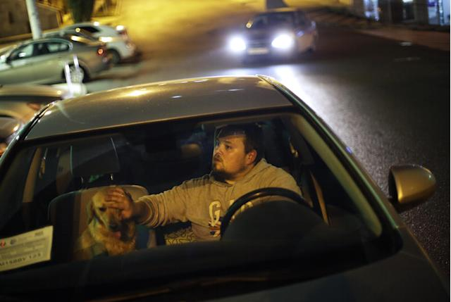 Alexei, an animal activist who would only give his first name, pets a stray half-breed Labrador he just picked up as he waits to meet up with his wife, his accomplice on this rescue mission, Monday, Feb. 10, 2014, in Sochi, Russia, home of the 2014 Winter Olympics. Alexei is one of a dozen people in the emerging movement of animal activists in Sochi alarmed by reports that the city has contracted the killing of thousands of stray dogs before and during the Olympic Games. Stray dogs are a common sight on the streets of Russian cities, but with massive construction in the area the street dog population in Sochi and the Olympic park has soared. Useful as noisy, guard dogs, workers feed them to keep them nearby and protect buildings. They soon lose their value and become strays. Tonight, a few dogs will be taken on their way to a new life in Moscow. (AP Photo/David Goldman)
