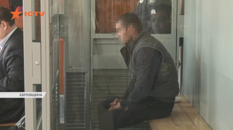 A man sits in court in Ukraine with his face pixelated.