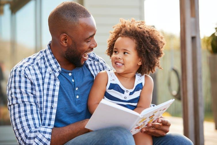 Father reads to small daughter
