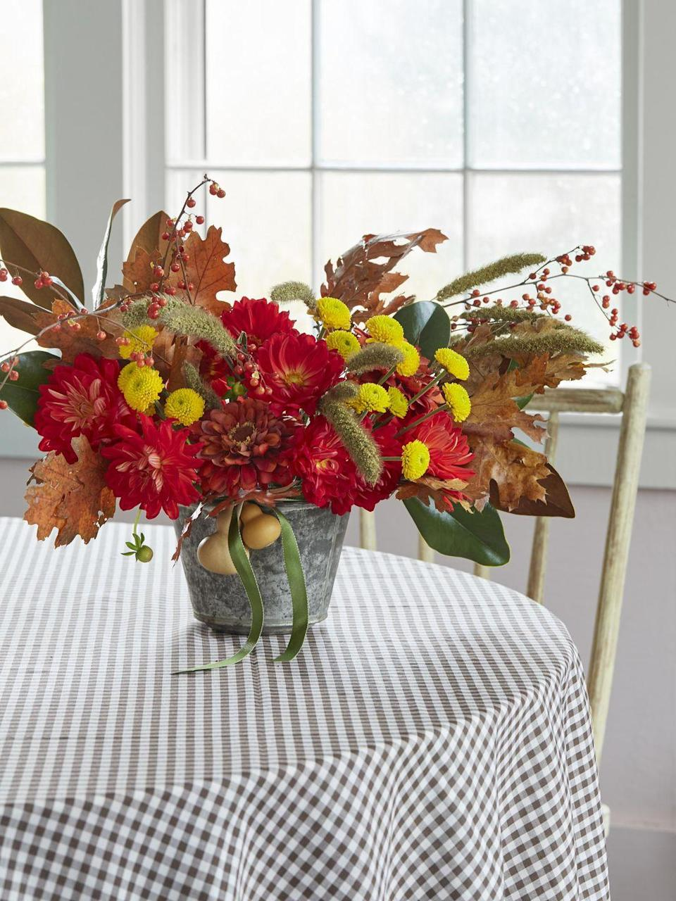 <p>Go for bold red and yellow blooms instead of the usual muted fall tones. In a vintage pudding tin or other favorite vessel, add flowers first, then mix in fall leaves, berries, magnolia leaves. Pro tip: Start with more stiff/branchy pieces to make a strong base, then move to softer, delicate materials. Finish it off with a ribbon tied with dried gourds.</p>