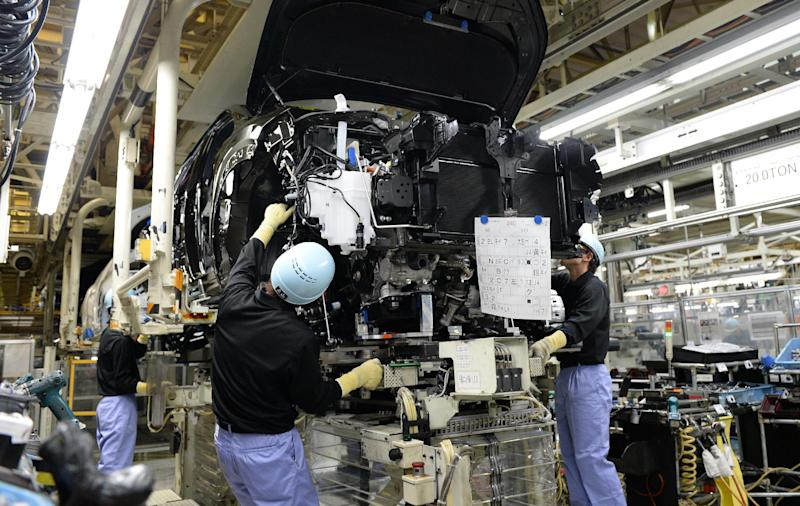 Employees of Toyota Motor Kyushu mount an engine into the body of a Lexus NX on an assembly line at the Miyata plant in Fukuoka Prefecture, Japan on August 8, 2014 (AFP Photo/Toru Yamanaka)