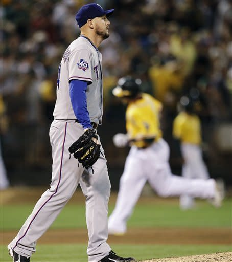Texas Rangers' Matt Harrison, left, walks back to the mound as Oakland Athletics' Jonny Gomes runs the bases after hitting a home run off Harrison in the sixth inning of a baseball game, Tuesday, Oct. 2, 2012, in Oakland, Calif. (AP Photo/Ben Margot)