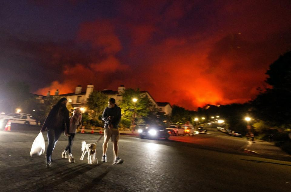 People evacuate their homes at night as a wildfire burns nearby